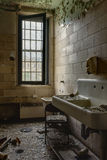 Bathroom with Sink - Abandoned Hospital / Sanitarium - New York. An interior view of a bathroom with a porcelain sink inside an abandoned hospital in New York royalty free stock images