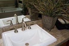 Bathroom sink and countertop. New home bathroom sink and countertop featuring unique faucet stock photography