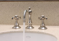 Bathroom Sink Faucet. The faucet on a new bathroom sink with water running stock photos
