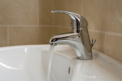 Bathroom sink tap with running water Royalty Free Stock Photos