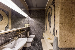 Bathroom with stone mosaic. Patterns on the walls and the floor with sink, mirror and toilet seat royalty free stock images