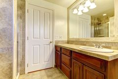 Bathroom with stone tiles and shower with wood cabinets. Royalty Free Stock Images