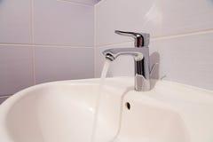 Bathroom tab. A modern basin mixer tap in a contemporary bathroom stock photos