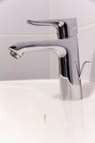 Bathroom tab. A modern basin mixer tap in a contemporary bathroom stock image