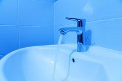 Bathroom tab. A modern basin mixer tap in a contemporary bathroom, bathroom faucet in blue tint stock image