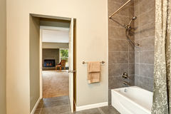 Bathroom with tile trim. View of opened door to bedroom with fireplace Royalty Free Stock Image