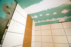 Bathroom tiles renovation. A bathroom being renovated, new tiles and raw walls, under construction Royalty Free Stock Images