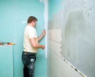 Bathroom tiles renovation. A man working at new bathroom tiles, putting them on the wall Royalty Free Stock Photo