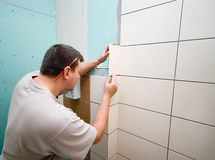 Bathroom tiles renovation. A man working at new bathroom tiles, putting them on the wall Stock Photography