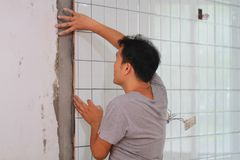 Bathroom tiles renovation. A man working at new bathroom tiles, putting them on the wall. HOME BUILDING & RENOVATION Royalty Free Stock Image