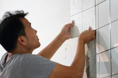Bathroom tiles renovation. A man working at new bathroom tiles, putting them on the wall. HOME BUILDING & RENOVATION Royalty Free Stock Photos