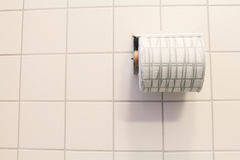 Bathroom tissue on anthracite tiled wall royalty free stock photos