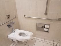Bathroom toilet with paper and metal railings. Bathroom or restroom toilet with paper and metal railings stock photography