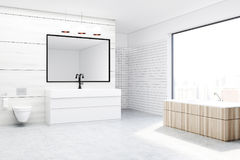 Bathroom with a toilet and a sink, white. Modern bathroom interior with wooden and white walls, a concrete floor, a sink, a wooden tub and a toilet. Large Stock Photos