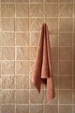 Bathroom towel hung on tiled wall Royalty Free Stock Photography
