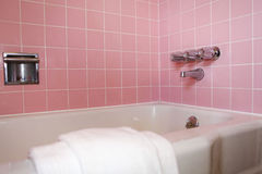 Bathroom tub with pink tile wall. Bright bathroom with pink tile wall, white rectangle tub royalty free stock photography