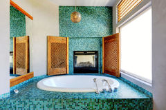 Bathroom turquoise tile wall trim with fireplace. Bathroom with turquoise tile trim and fireplace Stock Images
