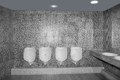 Bathroom urinal in a row with gray tiles Royalty Free Stock Photos