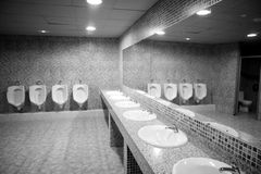 Bathroom urinal in a row with gray tiles. Black and white Royalty Free Stock Images