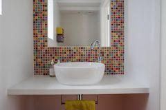 Bathroom wash basin with colorful glass mosaic tiles and mirror inset into the tiles. Bathroom ceramic wash basin with colorful hand made glass mosaic tiles and royalty free stock image