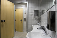 Bathroom with washbasin and wooden doors Royalty Free Stock Images