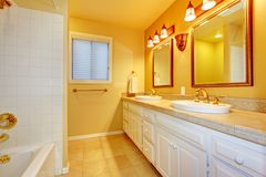 Bathroom with white cabinets and gold walls. Stock Images