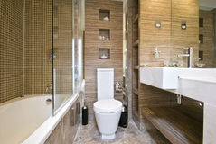 Bathroom with white suite. Bathroom with white ceramic suite and hard wood walls royalty free stock photo