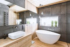 Free Bathroom With Wooden And Concrete Walls And White Bath Stock Photos - 177867513