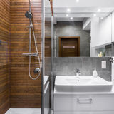 Bathroom with wood effect tiles. New style bathroom with wood effect tiles, shower, mirror and basin royalty free stock image