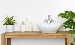Bathroom wooden table with washbasin, faucet, plants and soap bottles.  stock photography