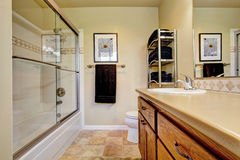 Bathroom wtih wooden vanity cabinet screened tub Stock Photo