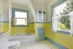 Bathroom with yellow walls, white tile floor, and full bath. Stock Photography