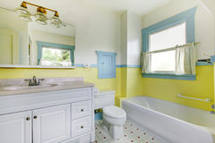 Bathroom with yellow walls, white tile floor, and full bath. Royalty Free Stock Image