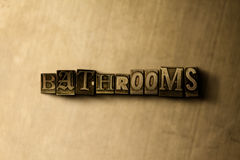 BATHROOMS - close-up of grungy vintage typeset word on metal backdrop Royalty Free Stock Image