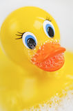 Bathtime bubbles with a Rubber Ducky. Fun bathtime with a closeup of a yellow rubber ducky in a bathtub full of water and soapy bubbles Royalty Free Stock Photos