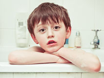 Bathtime. A six year old boy in the bath with a sad expression Royalty Free Stock Images