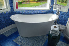 Bathtub. In a blue tiled modern bathroom Royalty Free Stock Images