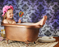 Bathtub Diva. An adorable preschooler eating a giant-sized lollypot in an clawfoot copper bathtub Royalty Free Stock Photo