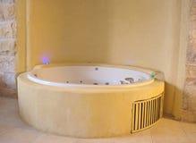 Bathtub jacuzzi in a modern bathroom. Bathtub jacuzzi in a modern design bathroom with stone wall Stock Image