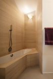 Bathtub with marble tiles on the walls Royalty Free Stock Images
