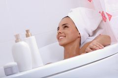 Bathtub relax. Tilt up of attractive girl with towel on her head lying in bathtub and smiling Stock Photos
