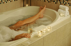Bathtub Relaxing Scene. Woman relaxing in a beautifully tiled tub. Sparkling wine, candles and towels adorn the scene stock image