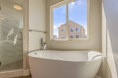 Bathtub and separate shower inside the bathroom of a new home. The large window provides a nice view of houses and bright sky on a sunny day stock photography