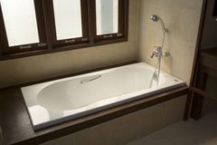 Bathtub and shower. Details of a built-in bathtub with a hand-held shower or spray, built near a window Stock Images