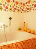 Bathtub with a shower and flower decors. Closeup of a mosaic bath with a shower, yellow children toys and flower tiles Royalty Free Stock Photo