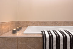 Bathtub, striped towel and candle lights Stock Photo