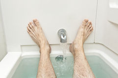 Bathtub With Water Running and Man's Feet Stock Image