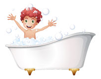 A bathtub with a young boy playing Stock Image