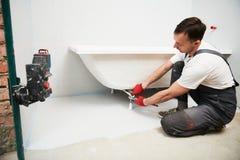 Bathtube installation. plumber installing and mounting bath with laser level. Plumber installing and mounting bathtube. home renovation of bath sanitary stock image