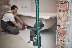 Bathtube installation. plumber installing and mounting bath with laser level. Plumber installing and mounting bathtube. home renovation of bath sanitary stock photo